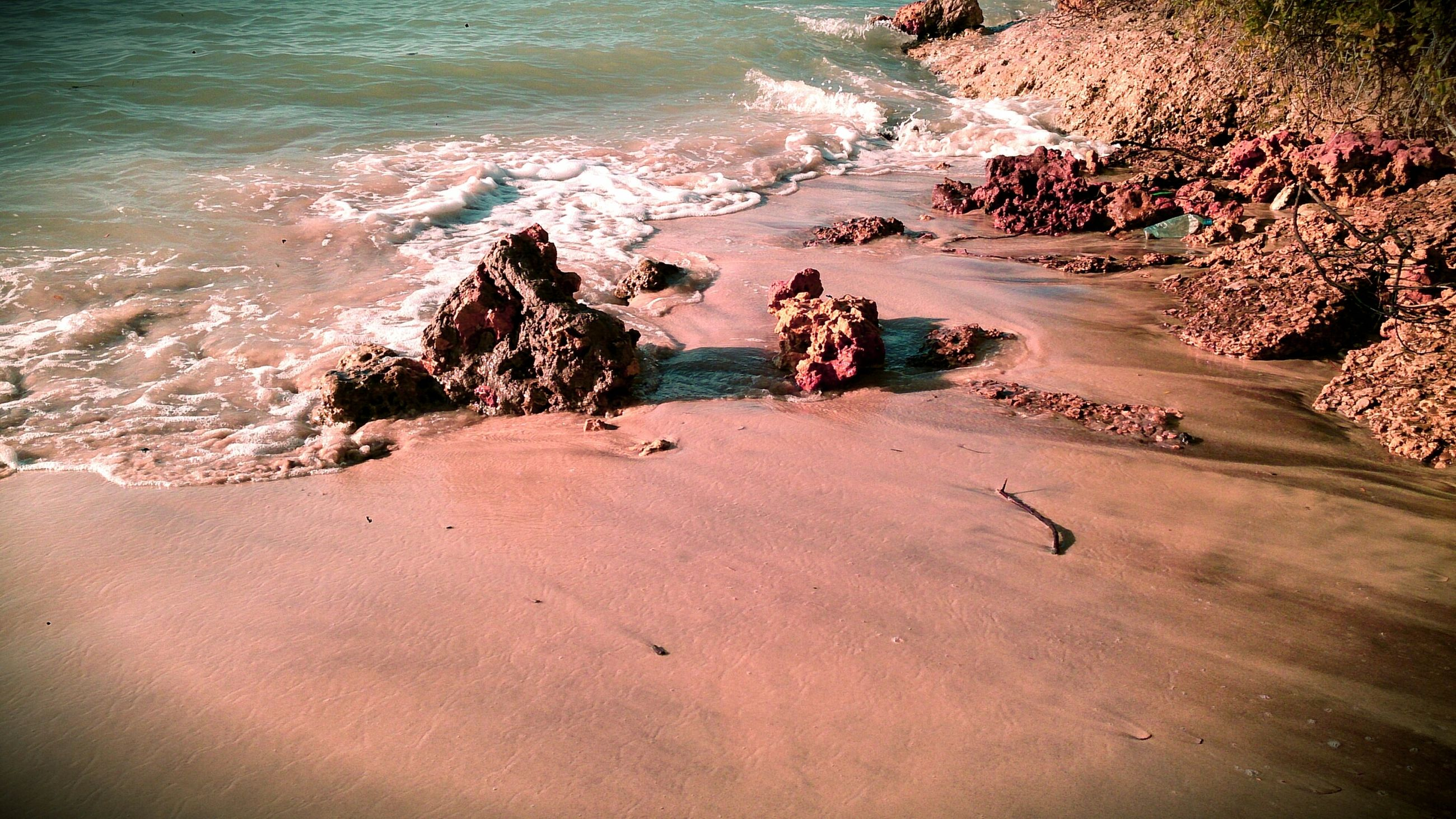 sea, beach, water, sand, shore, beauty in nature, high angle view, nature, tranquility, tranquil scene, surf, scenics, wave, sunlight, coastline, horizon over water, rock - object, vacations, idyllic, outdoors