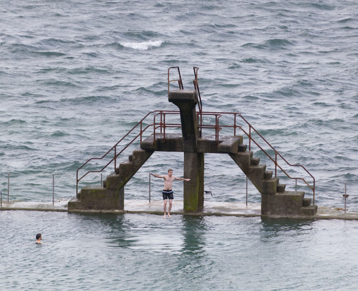 Young man jumping into seawater pool in Saint-Malo, France Aquatic Athlete Atlantic Ocean Board Diving Board Diving Platform Infinity Pool Jump Jumping Men People Platform Pool Sea Seawater Pool Sport Steps And Staircases Swimming Swimming Pool Swimwear Training Two People Water Young Adult Young Men