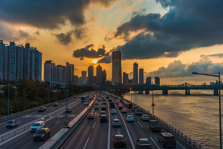 Vehicles on road amidst buildings against sky during sunset