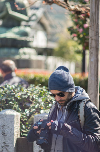 Beard Bearded Man Camera Camera - Photographic Equipment Casual Clothing Day Fingerless Gloves Hat Headshot Looking Down Man Outdoors Spring Sunglasses Tourist Warm Clothing Young Man