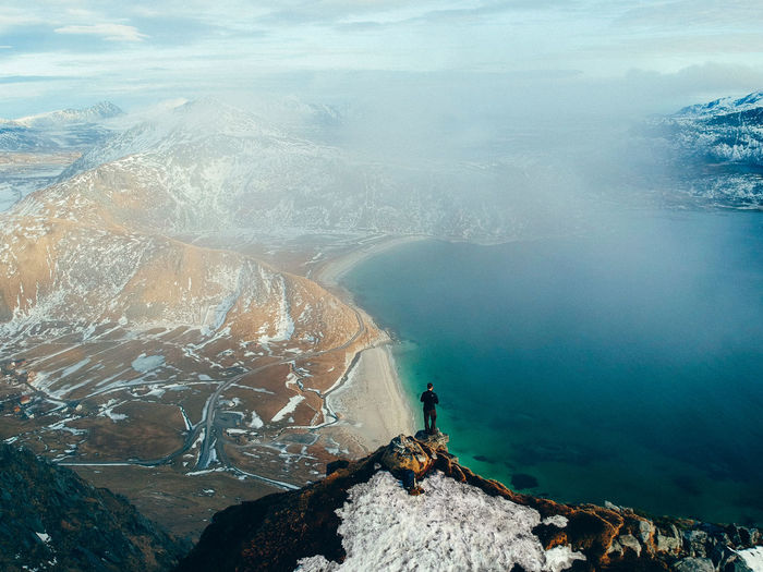 High angle view of man standing on mountain by sea
