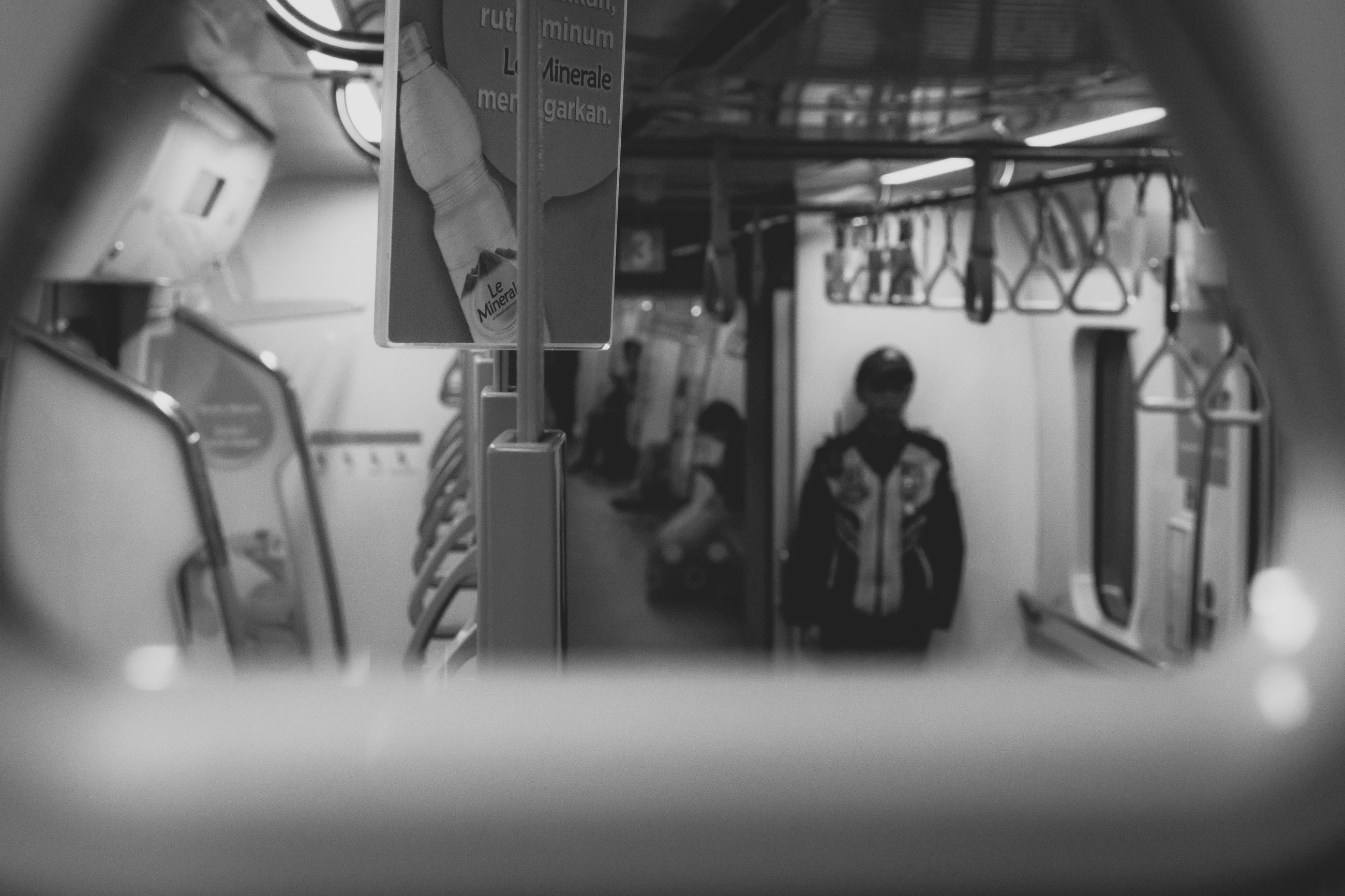 selective focus, public transportation, human representation, transportation, mode of transportation, representation, train, indoors, rail transportation, male likeness, real people, people, men, vehicle interior, group of people, group, train - vehicle, text, glass - material