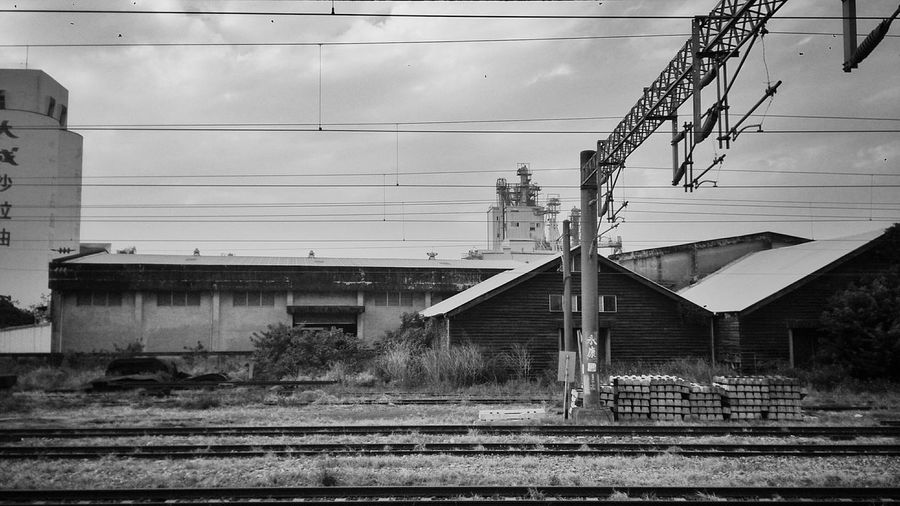 Railroad tracks by houses against cloudy sky