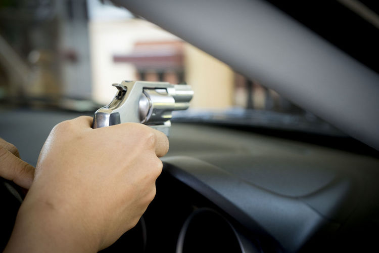 Cropped Hand Of Woman Holding Gun In Car