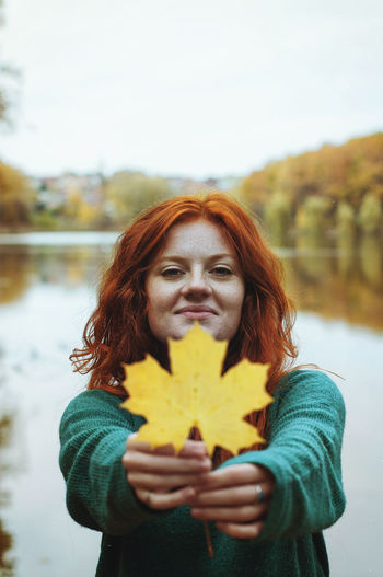 Redhead funny woman walking with yellow leaf near lake in autumn park.
