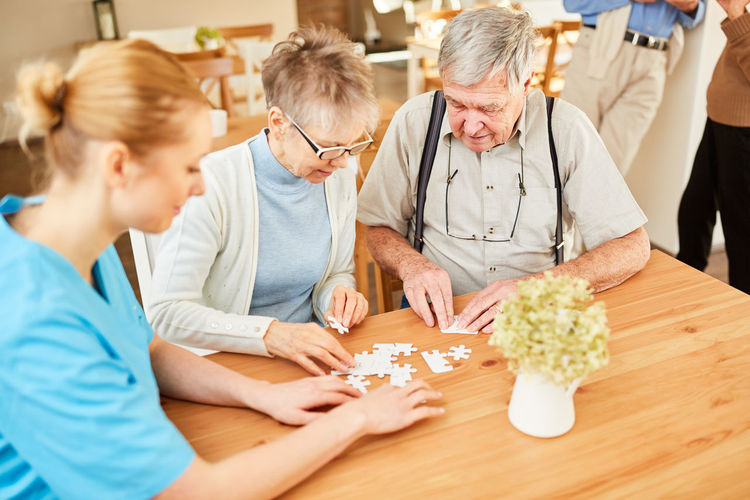 Senior people playing with jigsaw puzzle at nursing home