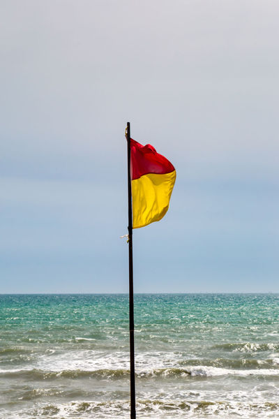 Red and Yellow Flag at the Beach Beach Beauty In Nature Clear Sky Day Flag Horizon Over Water Lifeguard  Nature No People Outdoors Safety Flag Scenics Sea Sky Swimming Tranquil Scene Tranquility Warning Warning Flag Warning Sign Water Wind