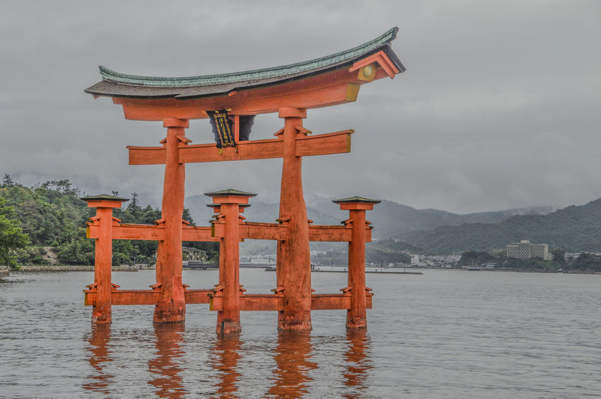 Tori At Miyajima Island Japan Bad Weather Cloud Japan Japanese  Miyajima Torii Gate Torri Beauty In Nature Clouds Day Island Mountain Nature Place Of Worship Religion Scenics Sea Shinto Shintoism Sky Spirituality Symbol Tori Travel Destinations Water