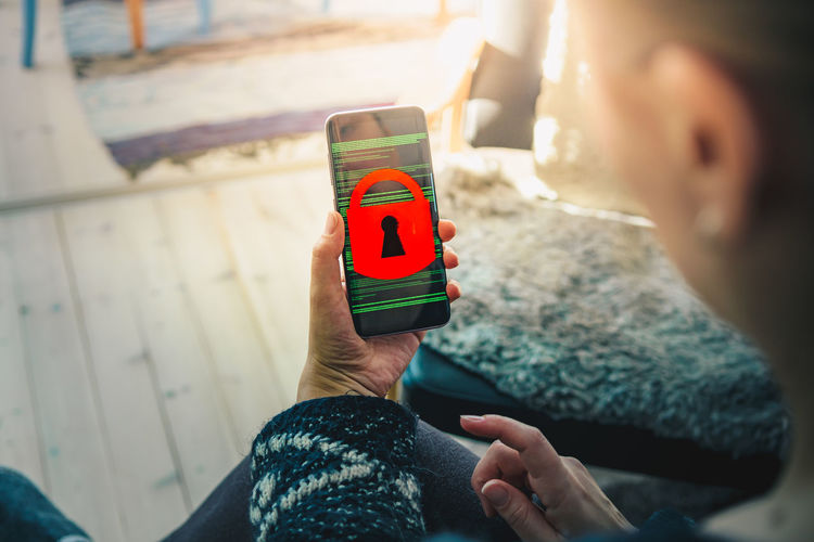 Smart device with padlock on screen Family Home Lifestyle Locked Security The Internet Woman Alarm Communication Cybersecurity Cyberspace Data Device Device Screen Encrypted Encryption Finger Holding Internet Lifestyles Over The Shoulder View Padlock Safety Security System Smart Phone