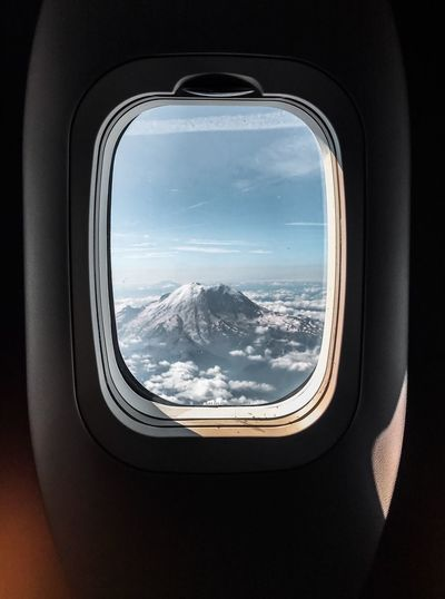 Snowcapped mountain seen through airplane window
