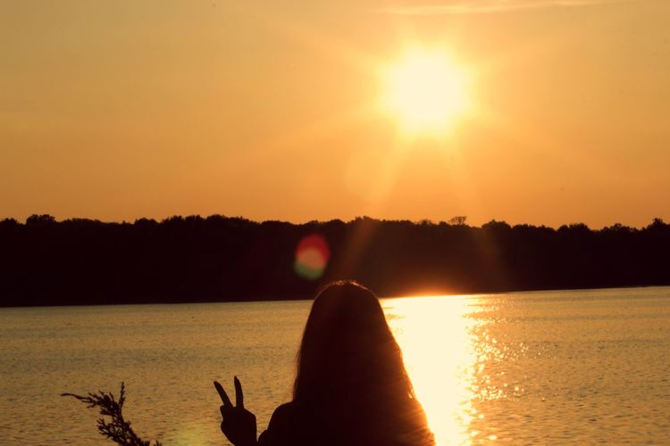 Silhouette woman showing peace sign by lake against clear sky during sunset