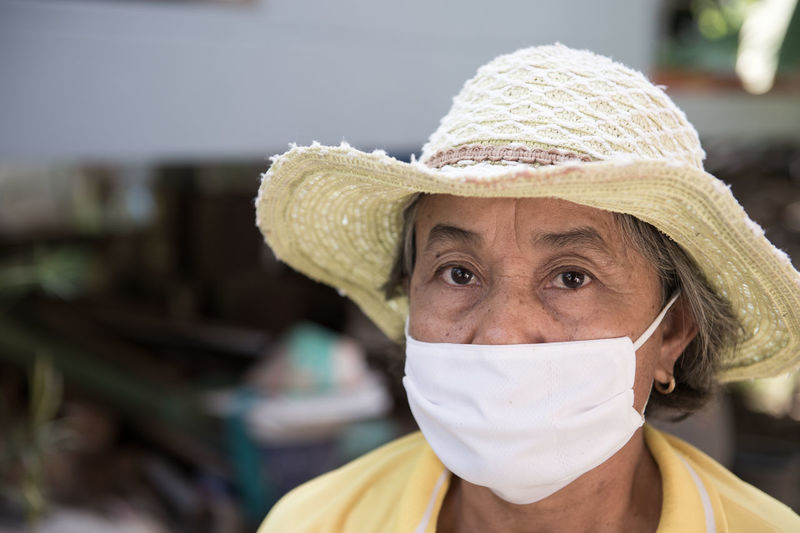 Portrait of senior woman wearing sun hat and surgical mask