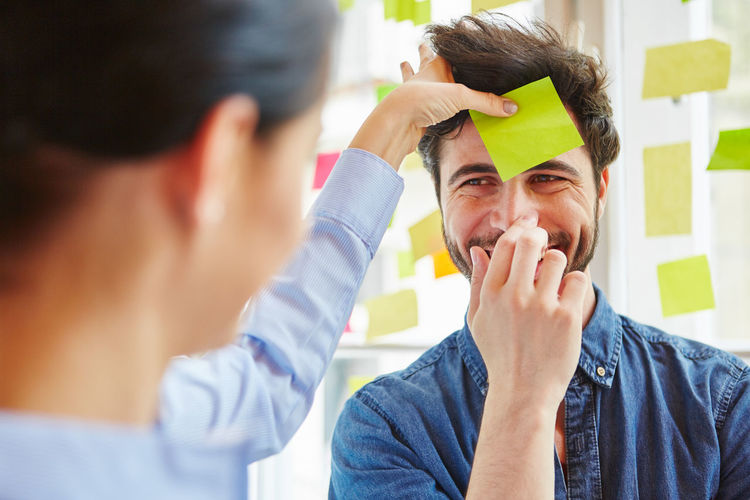 Businessman Sticking Adhesive Note On Businesswoman Face