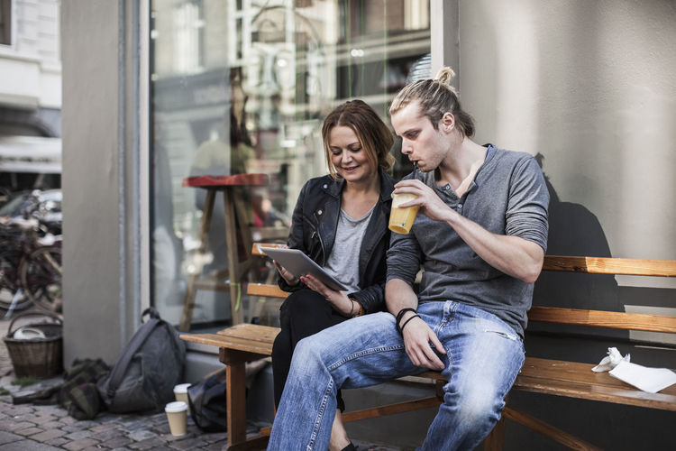 Young couple looking at camera while sitting on laptop