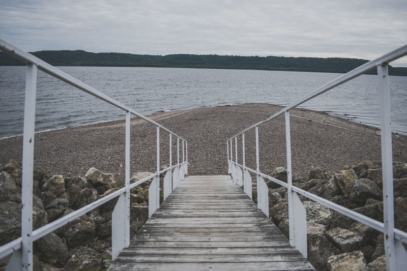 Staircase leading towards sea against sky