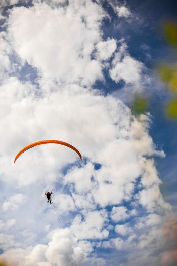Low angle view of paragliding against sky