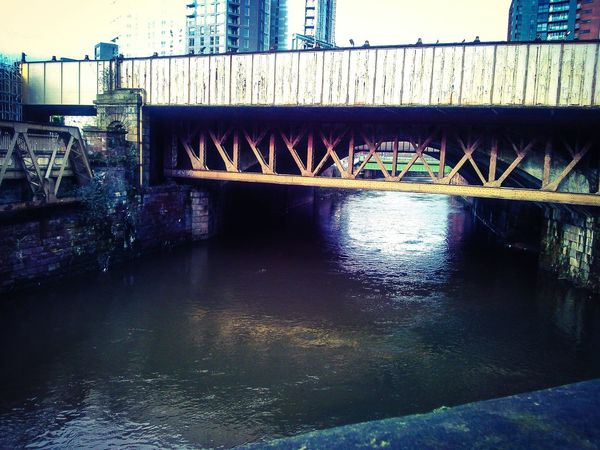 Photo of the dark, dark canal waters that snake through Manchester, travelling each bend in the town. Manchester Canal River Irk River Irwell Bridge Town Centre Dead Body Dumping Ground Serial Killer The Pusher Manchester