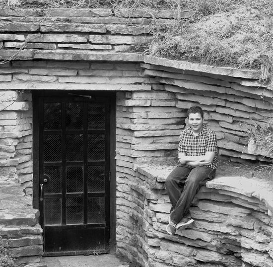 Portrait Of Smiling Man Sitting Outside House