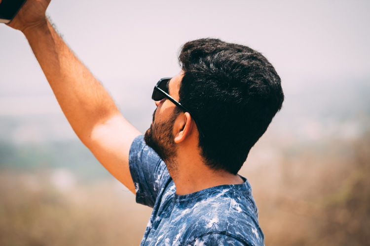 Side view of young man taking selfie while standing outdoors