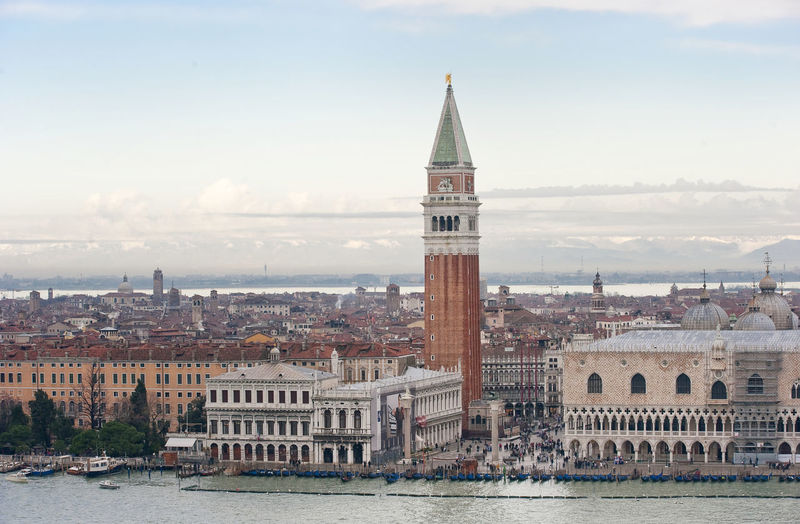 St mark cathedral and campanile by grand canal against sky