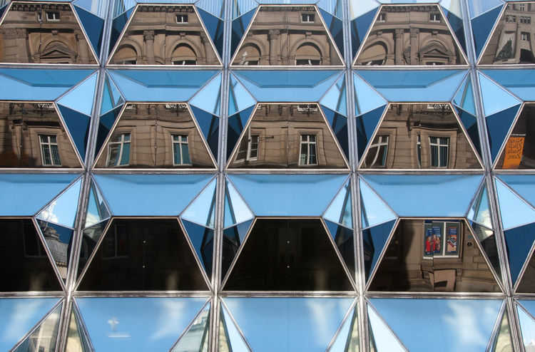 Reflections in Windows Architectural Feature Architecture Backgrounds Blue Building Building Exterior Built Structure City Day Design Façade Full Frame Geometric Shape Glass Mirrored Modern No People Office Building Order Outdoors Pattern Reflection Repetition Window