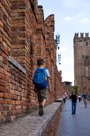 Traveling with kids - Boy walking on Castelvecchio Bridge ledge Backpacking Castelvecchio Castelvecchio Verona Castle Exploring Family Kids The Traveler - 2018 EyeEm Awards Travel Traveling Traveling Home for the Holidays Verona Walking Around Backpack Boy Boys Brick Castel Childhood Italy Kid Ledge Lifestyles One Person Travel Destinations