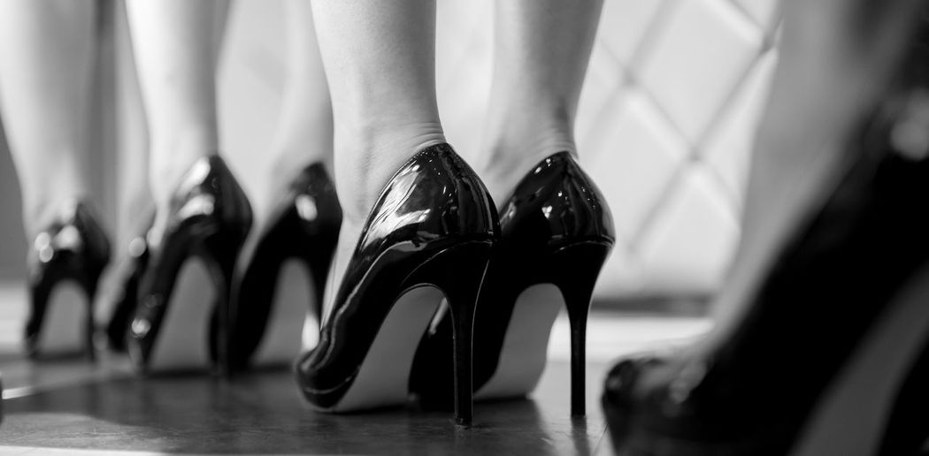 Low section of fashion models wearing high heels