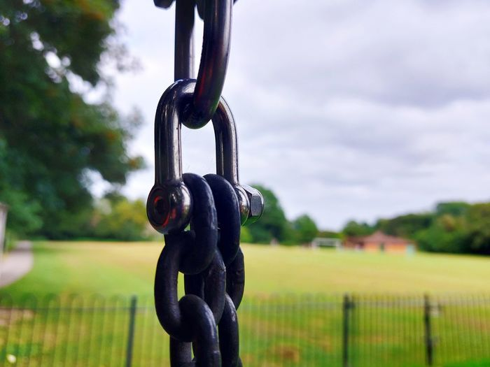 Close-up of metal chain on field against sky