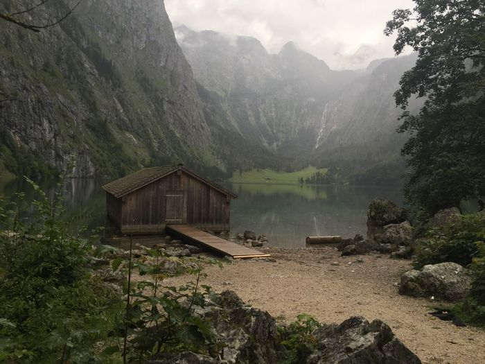 Wooden house amidst calm lake against mountain