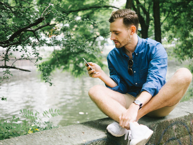 phone fun Bad Habit Beauty In Nature Casual Clothing Communication Day Full Length Leisure Activity Lifestyles Men Mobile Phone Nature One Man Only One Person Outdoors Portable Information Device Real People Relaxation Sitting Smart Phone Technology Tree Water Wireless Technology Young Adult Young Men