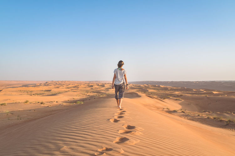 Rear view full length of woman walking at desert against clear sky
