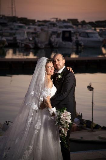 Portrait Of Smiling Bride And Groom Embracing Against River At Dusk