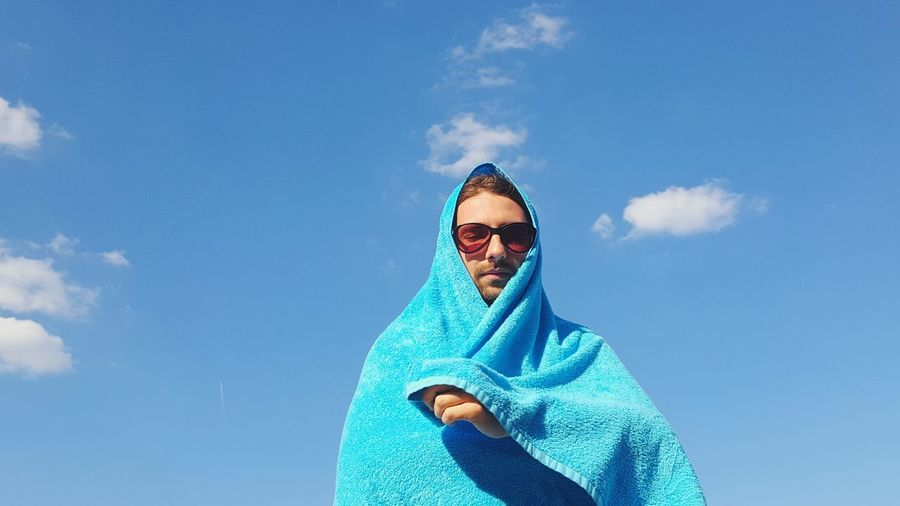 Low Angle View Of Man Wrapped In Towel Against Blue Sky On Sunny Day