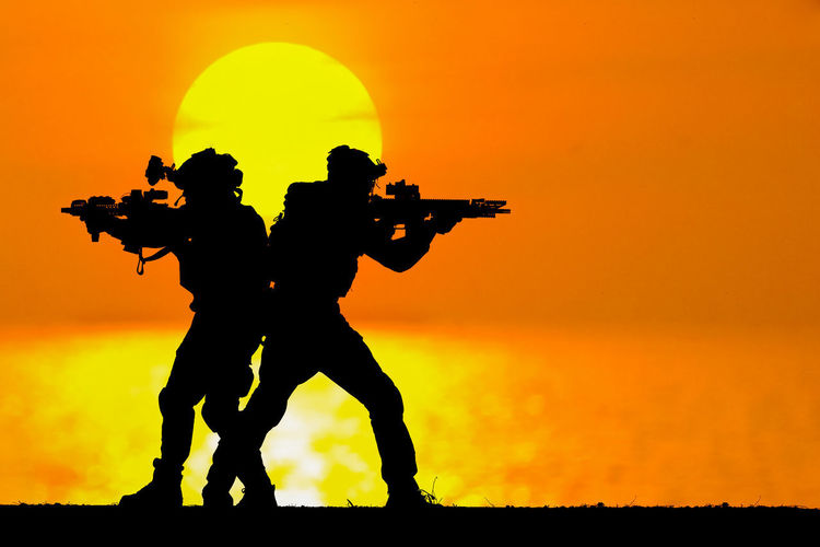 Silhouette men standing against orange sky during sunset