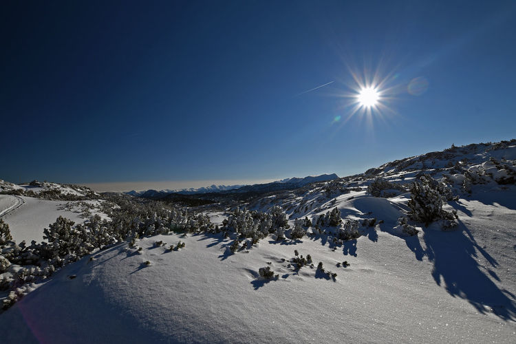 Scenic view of snow covered mountains against bright sky