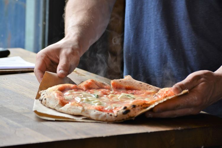 Midsection of man holding pizza at table