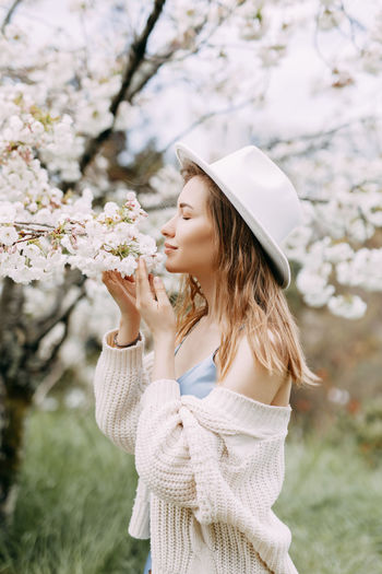 Gentle girl in a dress and a fashionable hat is walking enjoying the smell of blooming flowers