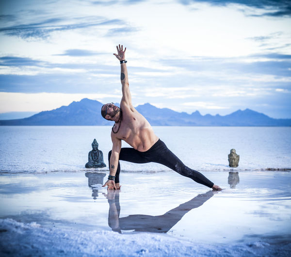 Shirtless mature man practicing yoga on shore at beach against sky