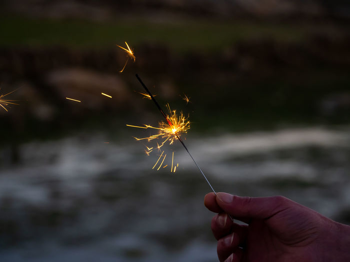 Person holding sparkler at night