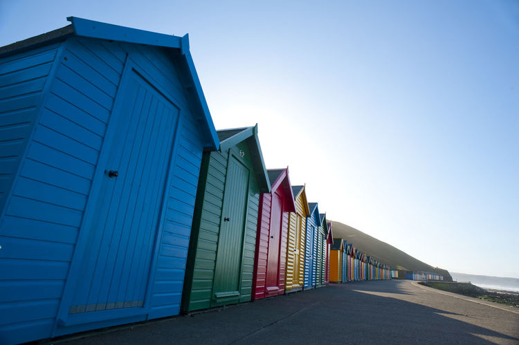Row of colorful wooden beach huts in Whitby, North Yorkshire overlooking the Whitby sands for use by bathers and tourists during the summer season Architecture Architecture Bathing Blue Built Structure Cabins  Clear Sky Closed Coast Colorful Diminishing Perspective Empty Huts LINE No People North Yorkshire Outdoors Receding Swimming Tourists Traditional Uk Whitby Whitby Sands Wooden