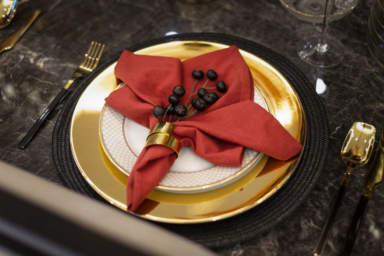 High angle view of napkin and fruit in plate on dining table