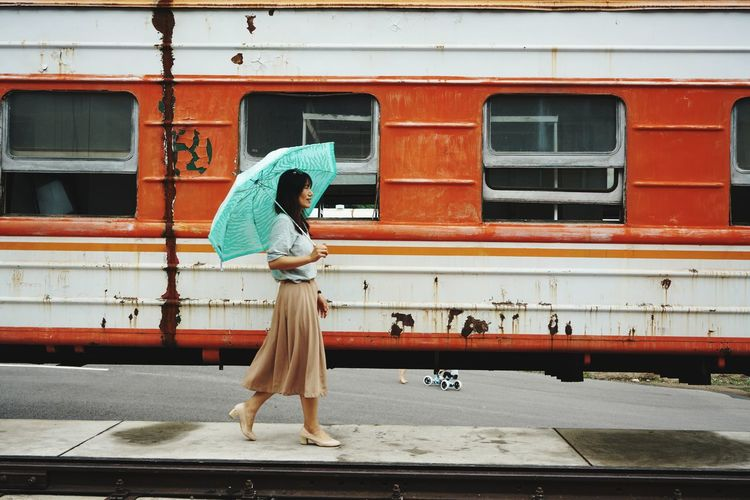 Side view of woman with umbrella walking at railroad station