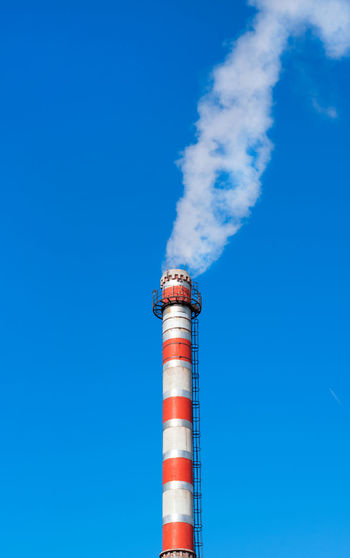 Factory chimney releasing steam against the clear blue sky
