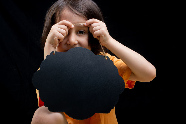 Portrait of a girl holding black background