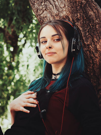Close-up of smiling hipster listening music on headphones