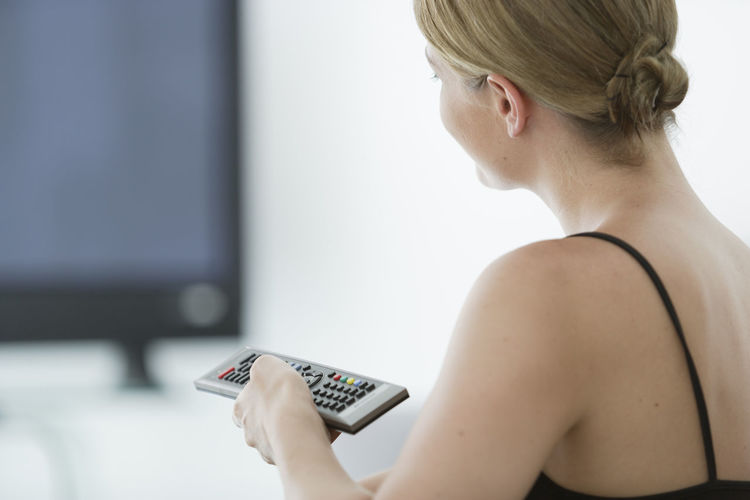 Close-Up Of Woman Changing Tv Channel At Home