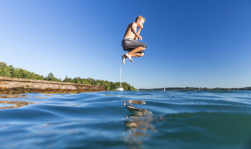 Full length of shirtless boy jumping over lake against clear blue sky