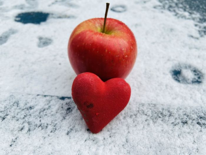 Close-up of apple on heart shape in winter
