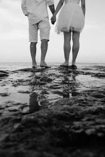 Low Section Of Couple Holding Hands While Standing On Rock By Sea