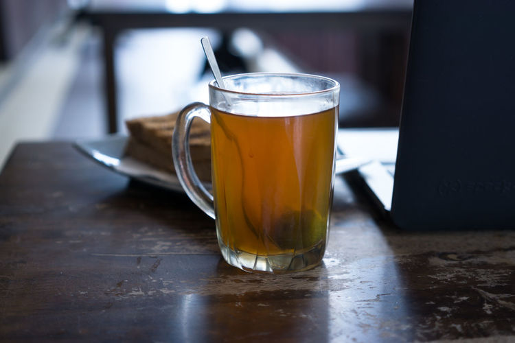 High Angle View Of Drink By Laptop On Wooden Table